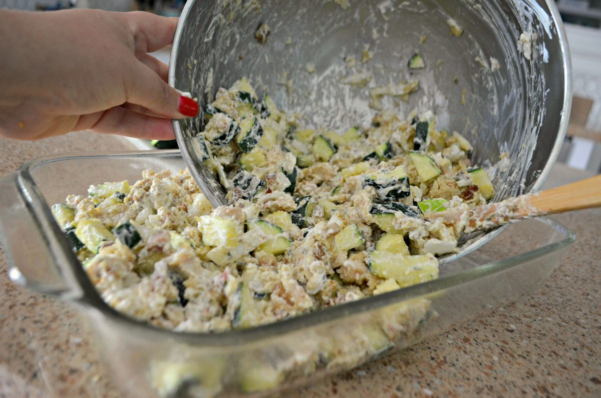 easy chicken zucchini casserole recipe -- ingredients being spooned into the baking pan