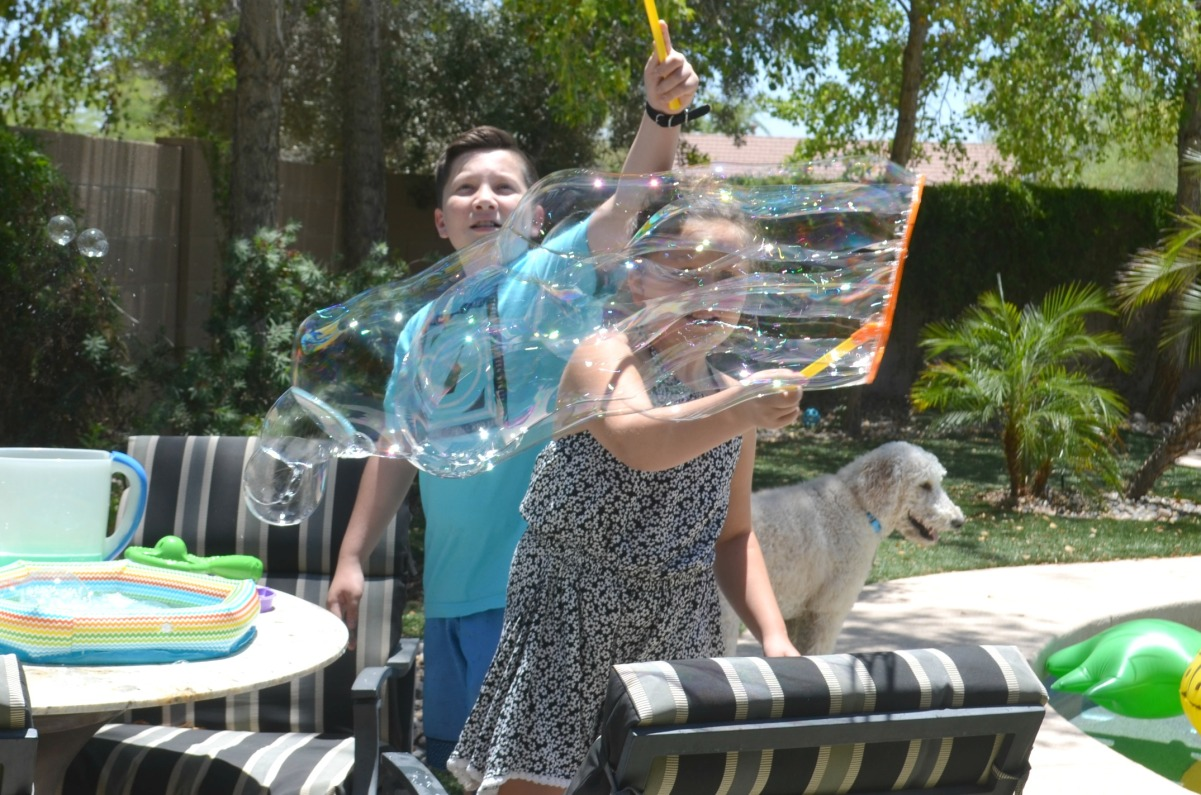 kids playing with giant bubbles outside