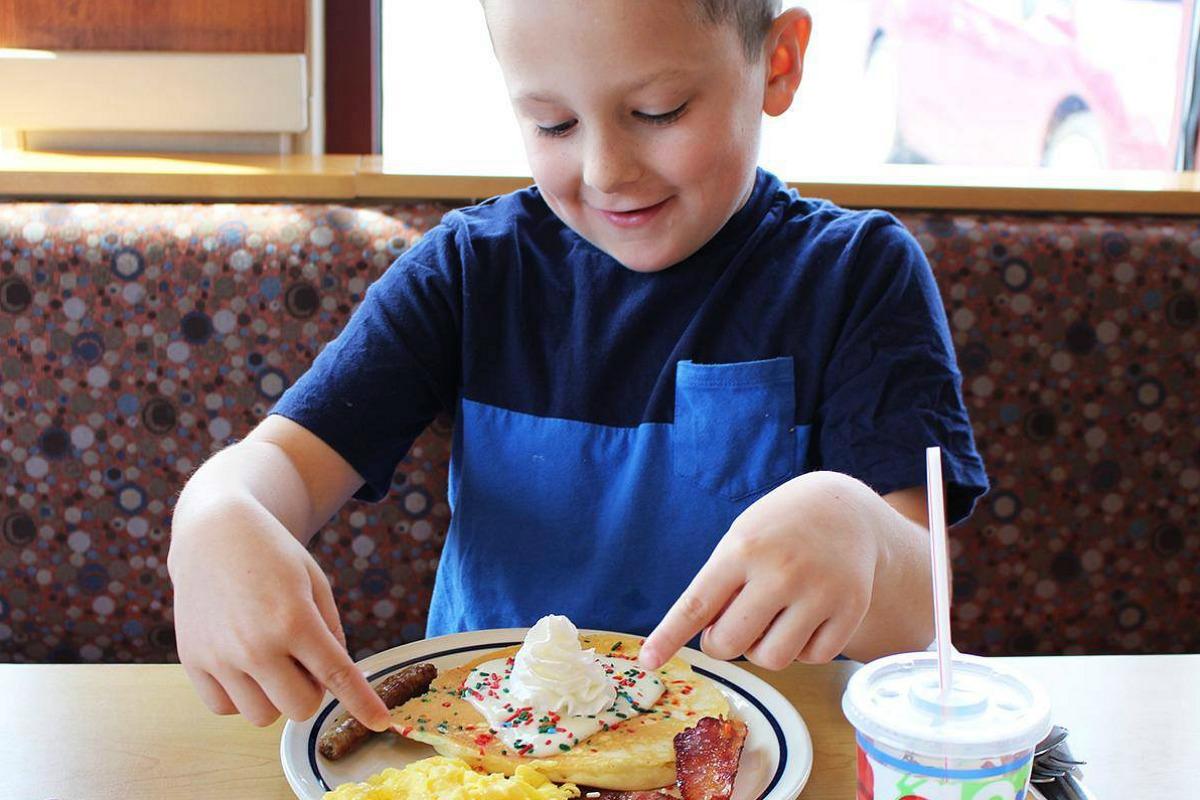 child eating pancakes