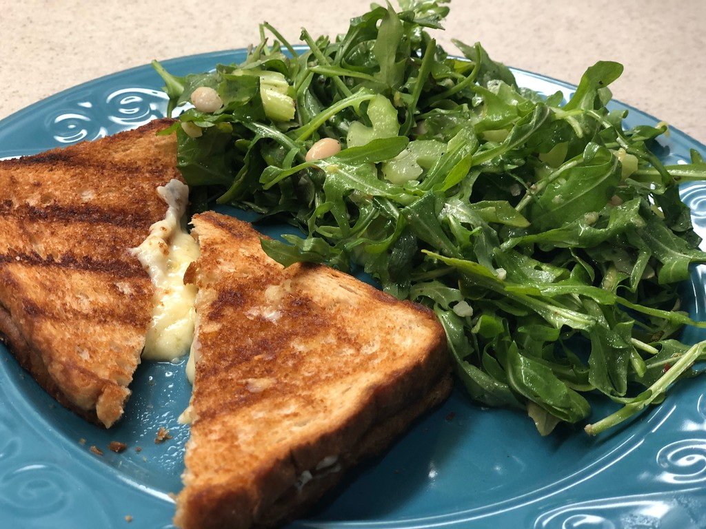 grilled cheese with arugula salad on plate