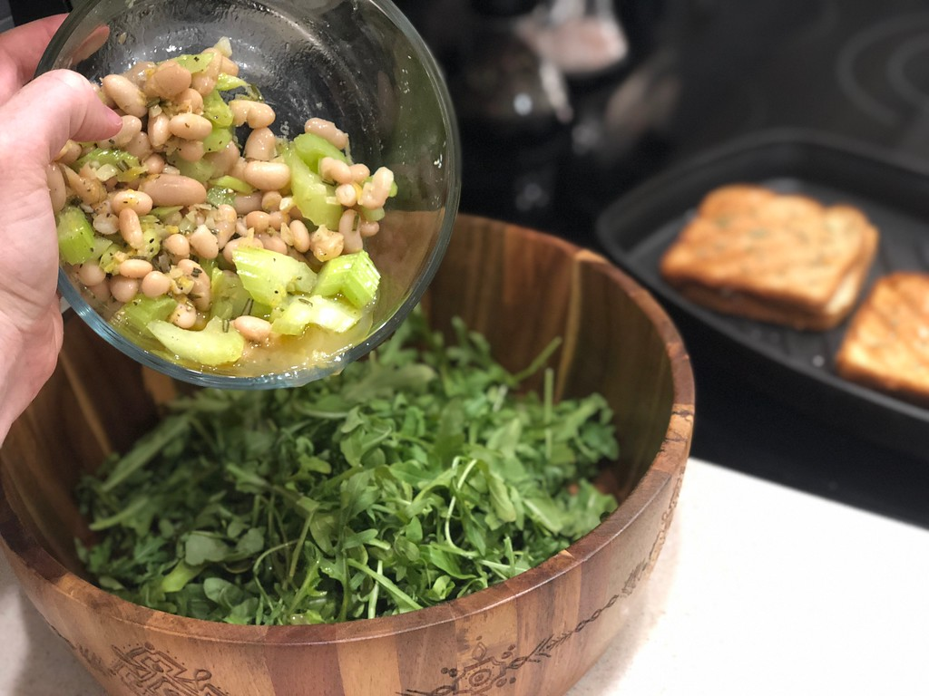 pouring beans into salad with grilled cheese
