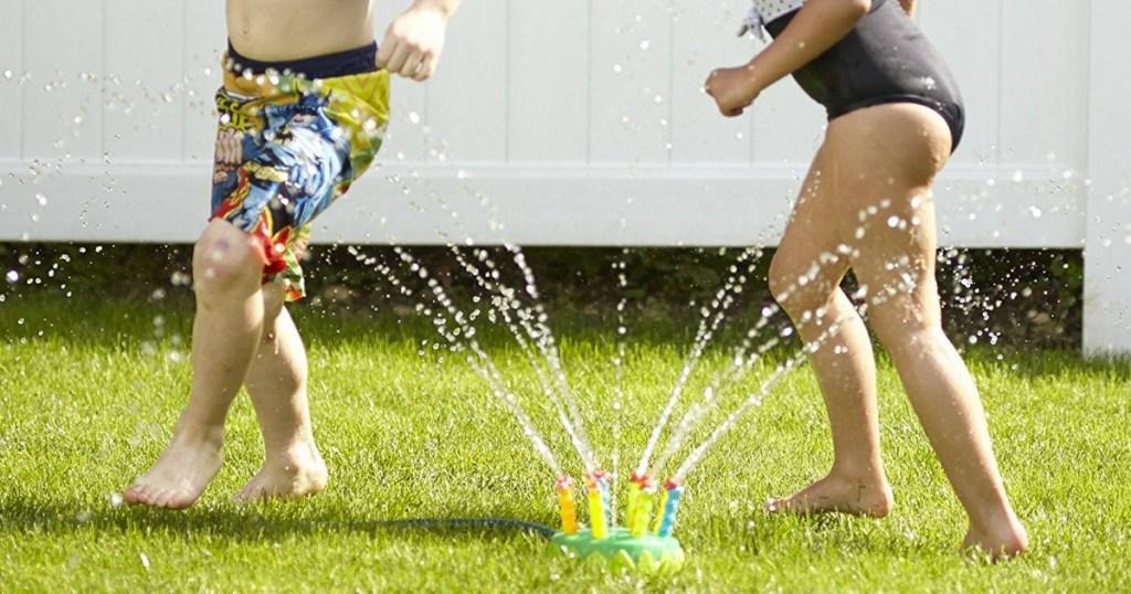 kids running thru a melissa and doug sprinkler