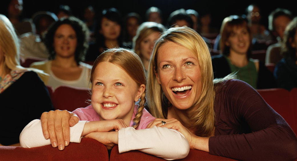 mom and daughter smiling and watching a movie