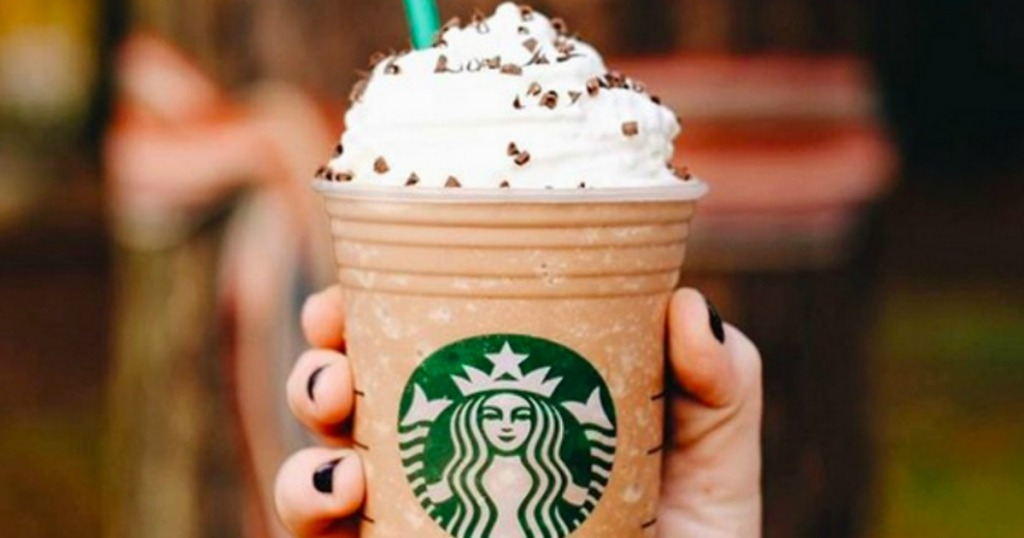 holding Starbucks drink with whipped cream