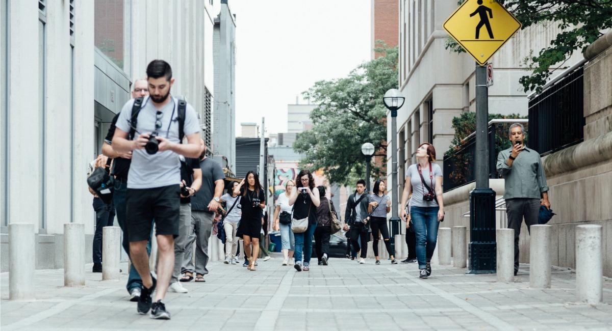 man checking his camera as he walks along the street