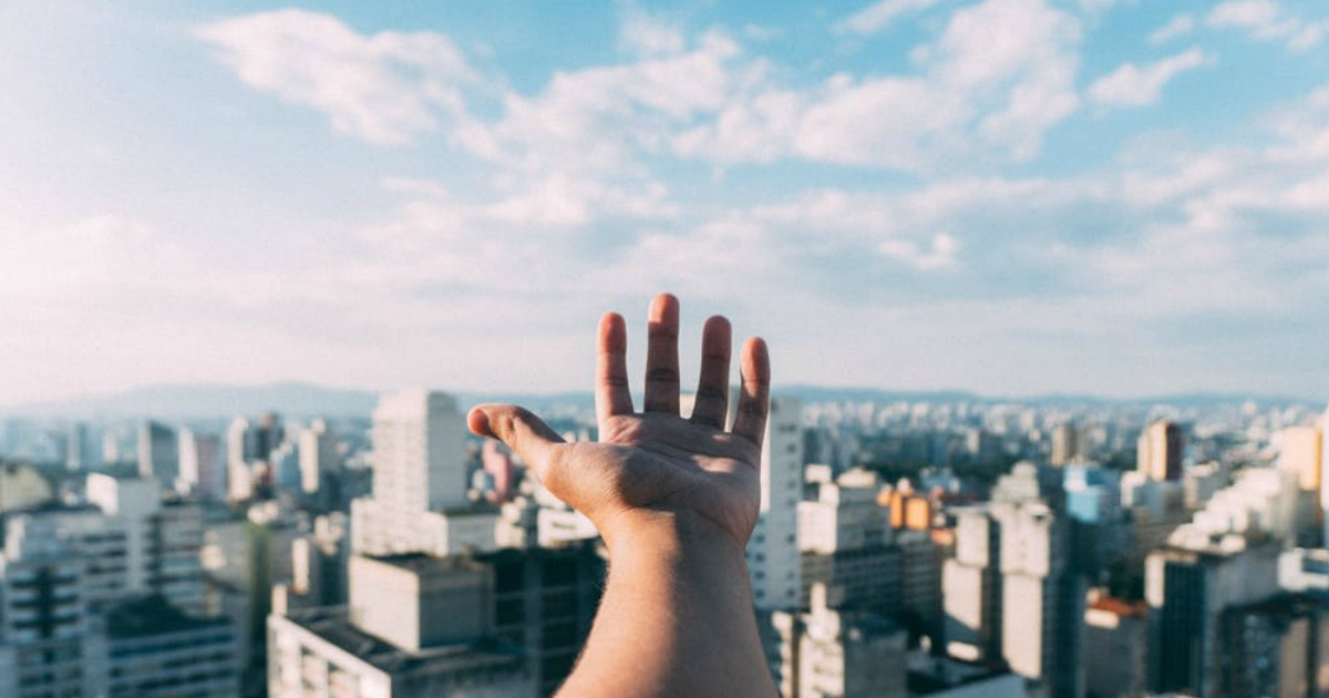 hand reaching out over city skyline