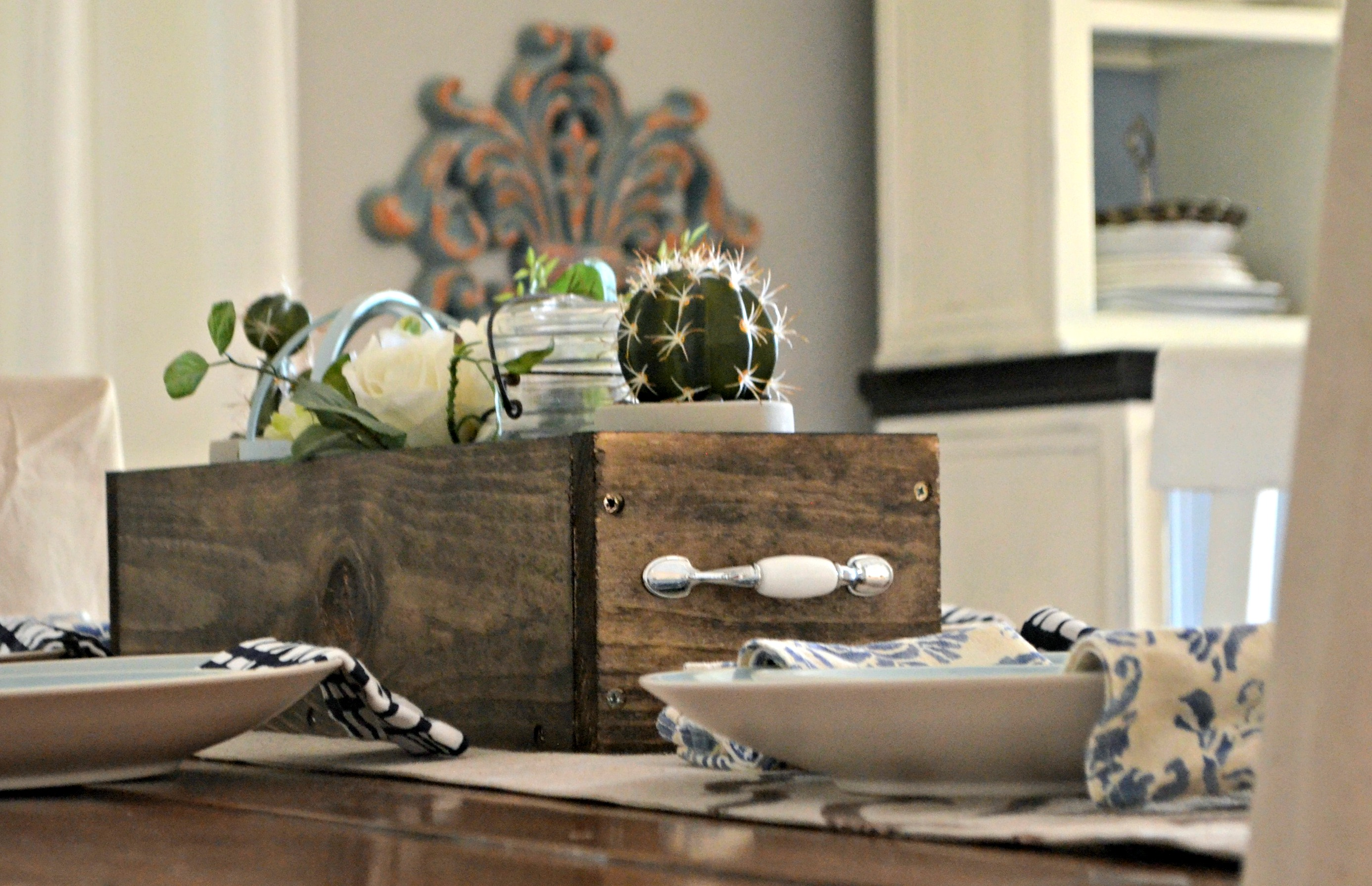 diy rustic farmhouse wood box centerpiece – filled with cute items like cacti, a vase, and a candle