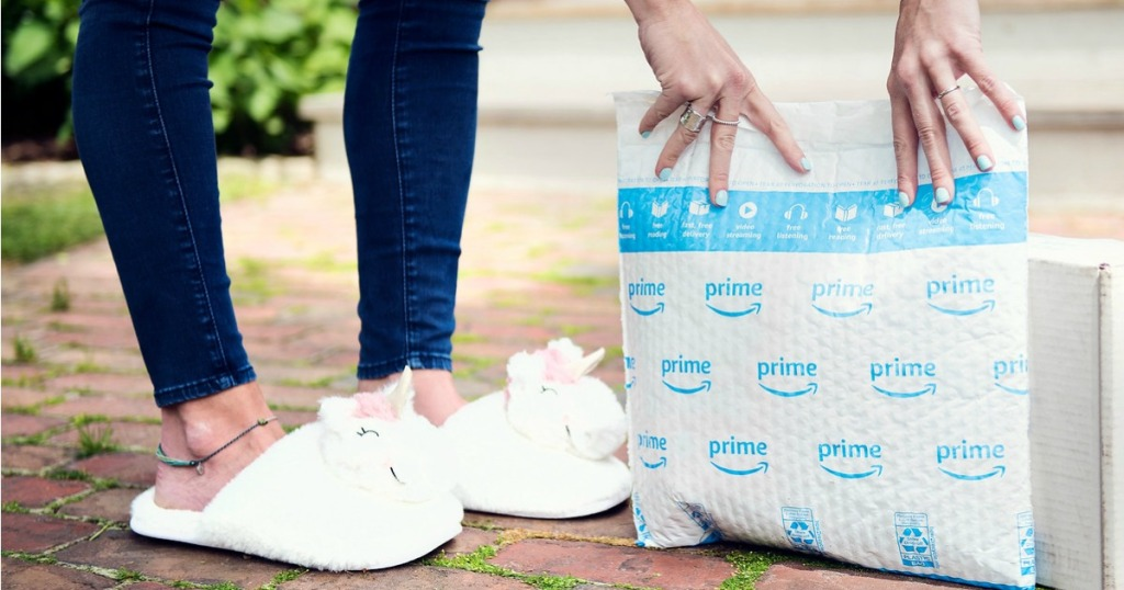 Woman wearing unicorn slippers while holding up an Amazon Prime package