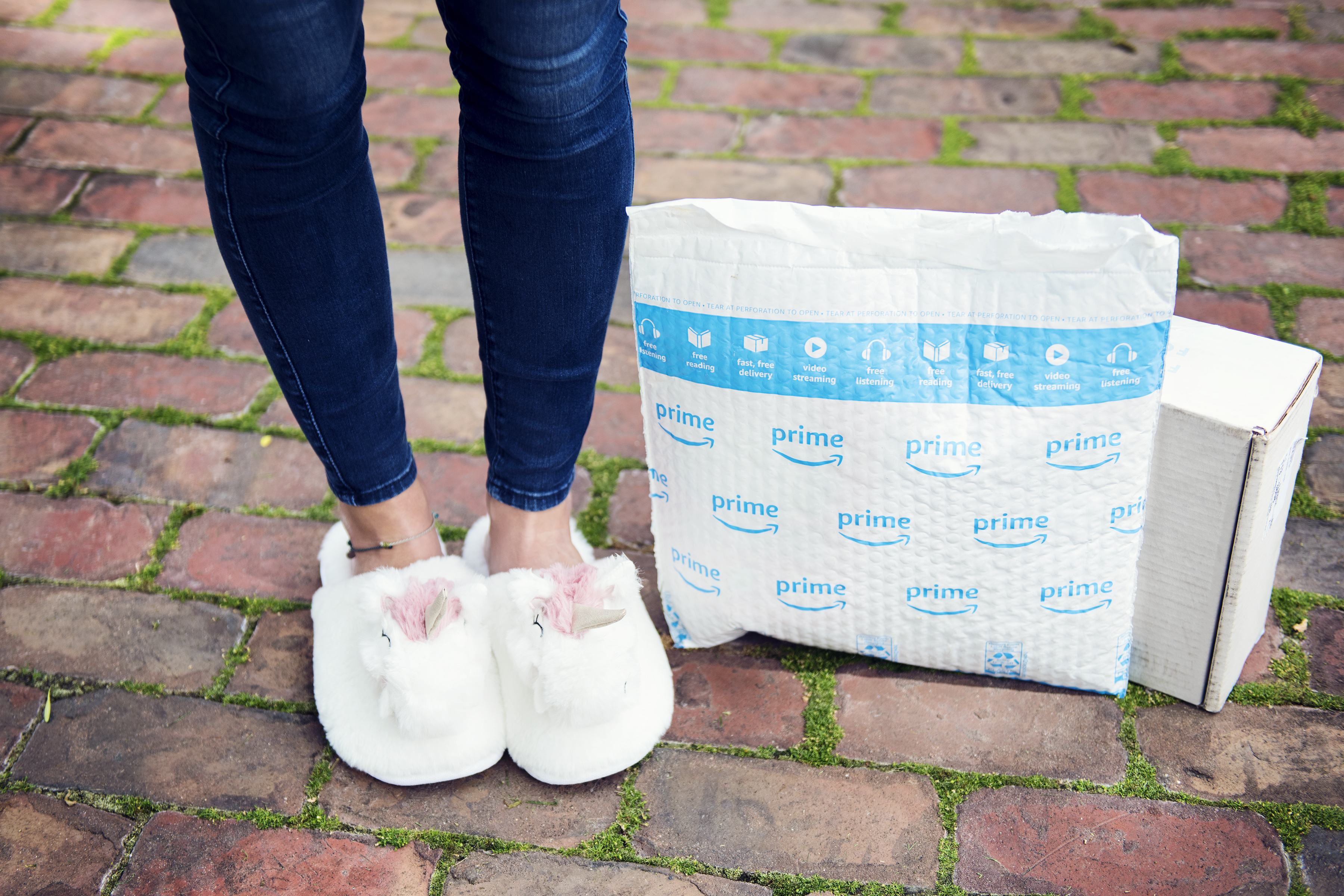 amazon prime day deals are coming! - Collin in unicorn slippers next to a prime package