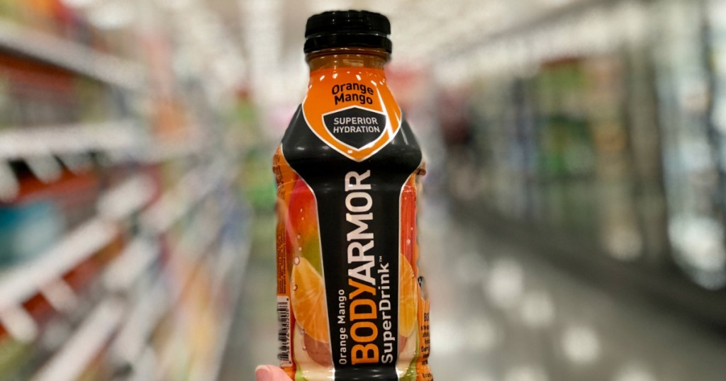 hand holding bottled drink up in store aisle