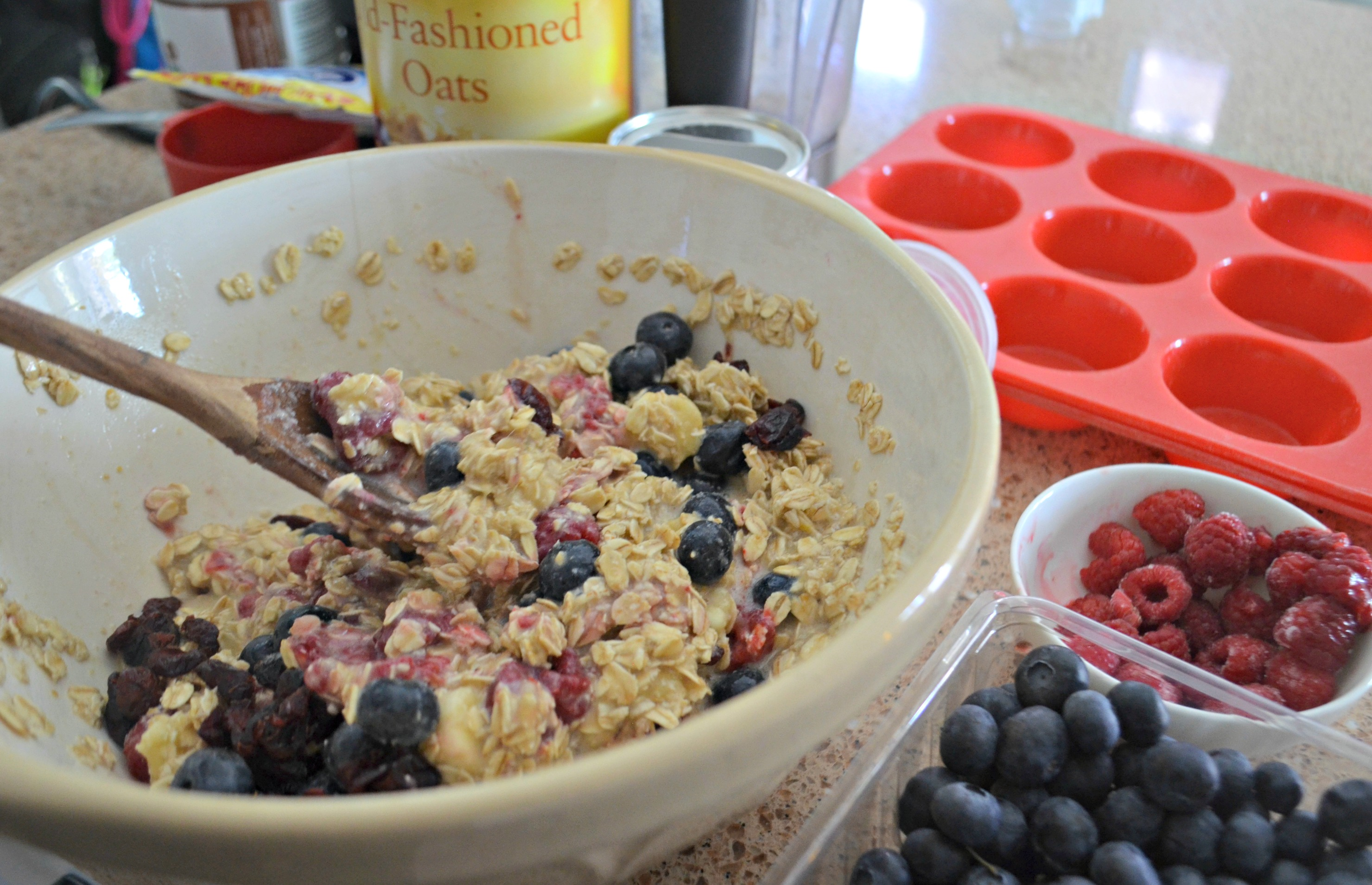 Baked Oatmeal Berry Cups – mixing the ingredients in a bowl with a wooden spoon