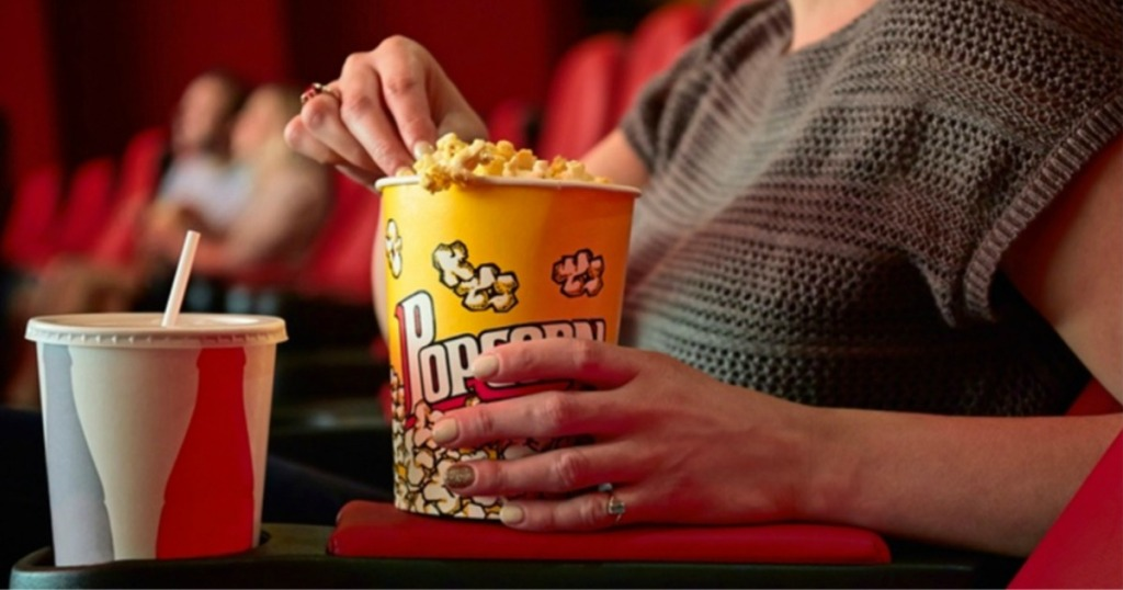 person at movies with popcorn and drink