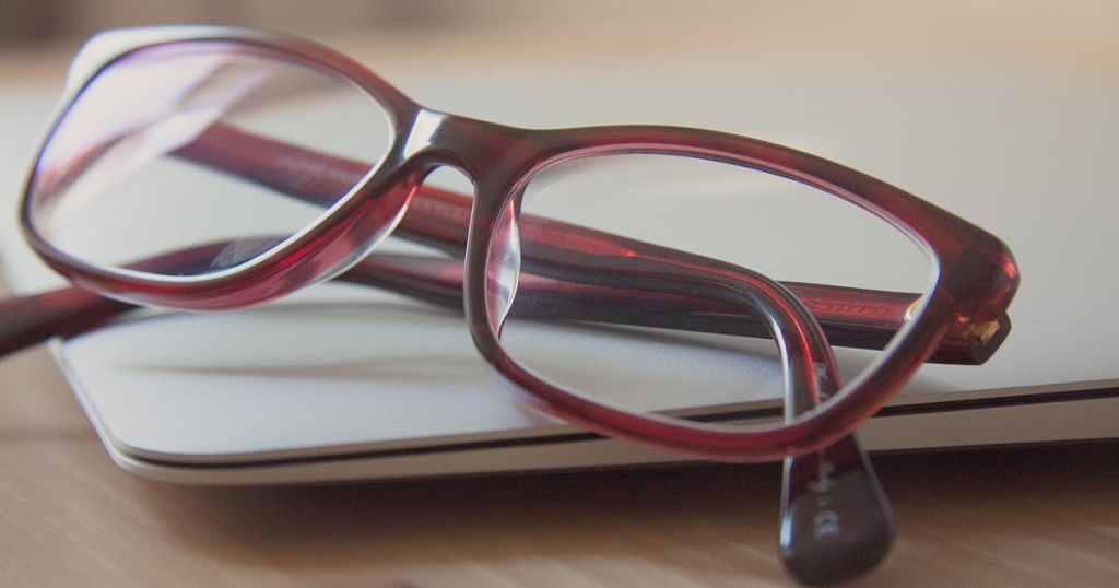 Red frame glasses folded and resting on a computer