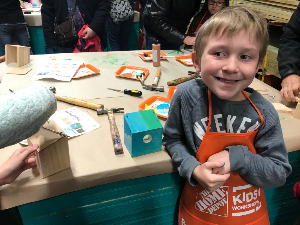 little boy smiling wearing an apron from Home Depot workshop