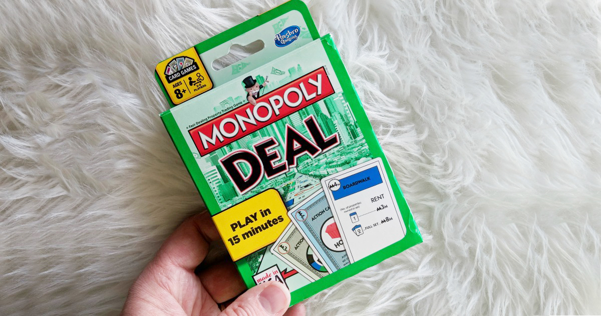 hand holding card game on white rug