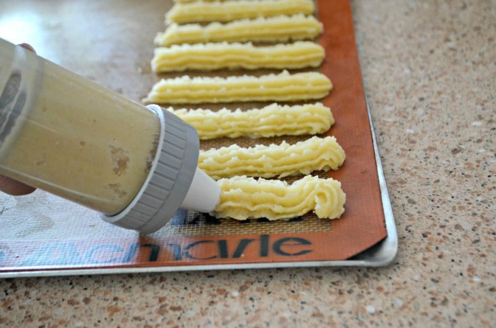 piping out churros onto baking sheet before air frying
