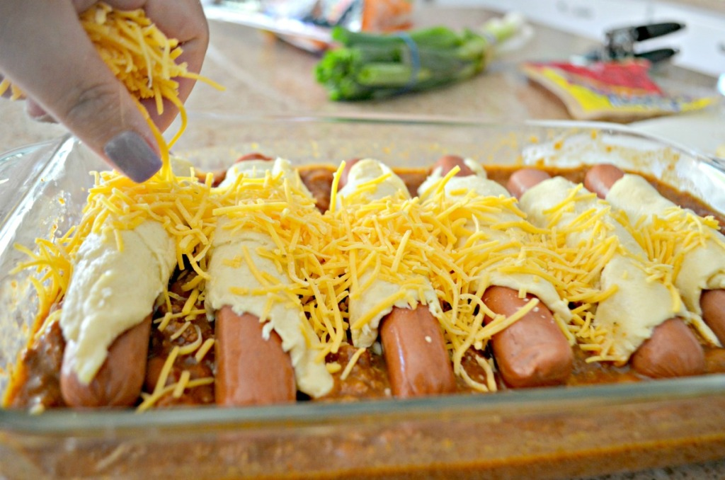 sprinkling cheese on top of baked chili dogs