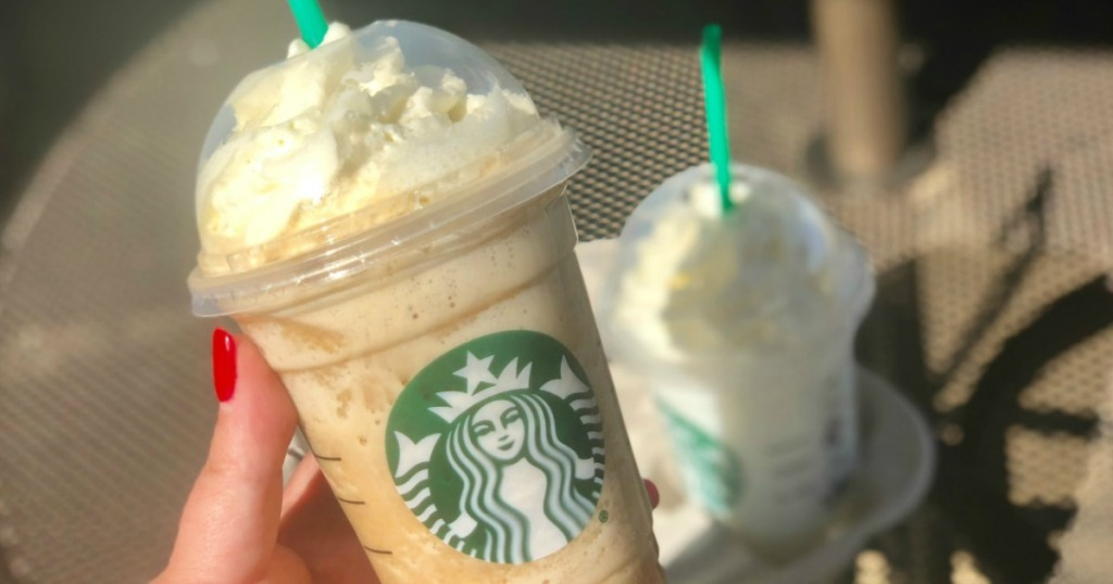 starbucks frozen beverage with whipped cream being held outside