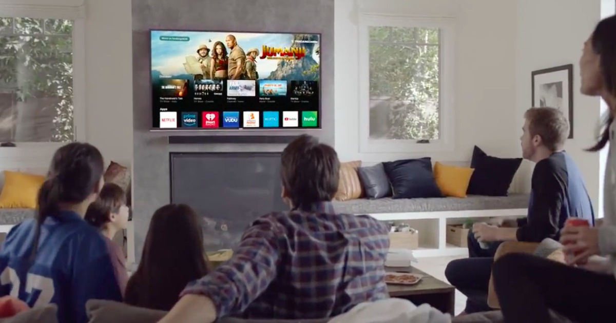people sitting in a living room watching a big screen tv