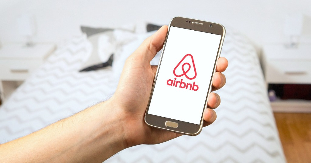 hand holding phone with airbnb app