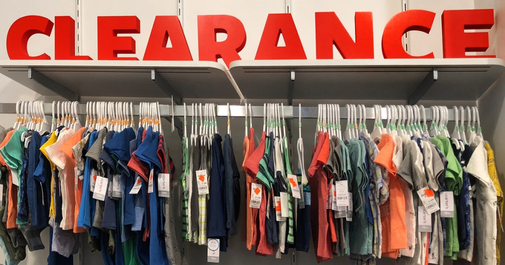 Wall of clothes with clearance signage at Carter's