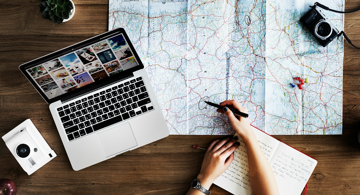 Money saving tips and hacks for airplane flights - planning out vacation with map and computer