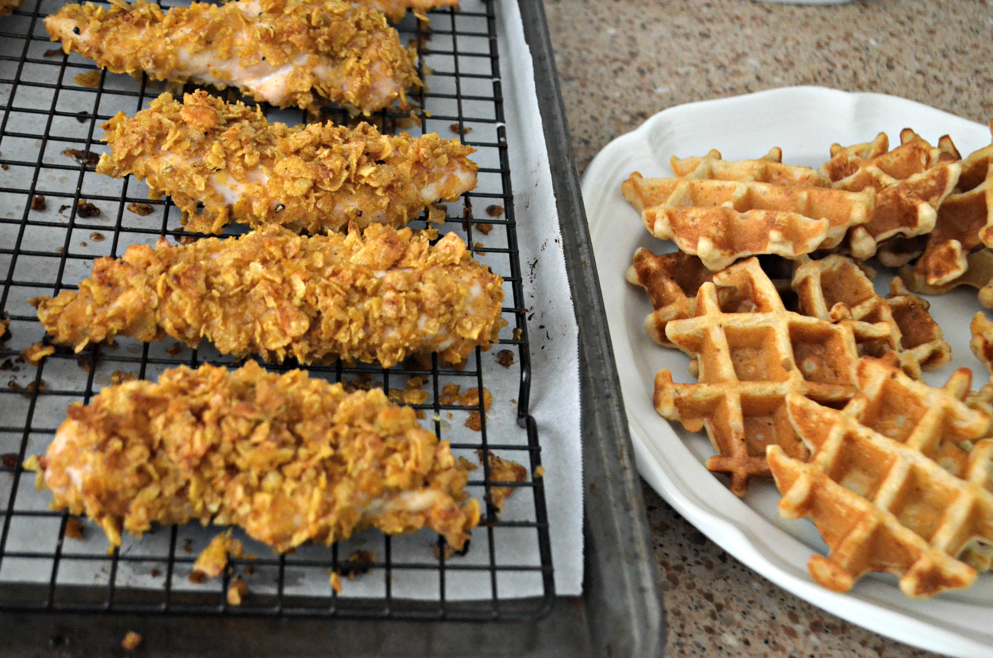 Easy Cornflake Chicken and Mini Waffles - chicken on the baking rack next to the waffles on a plate