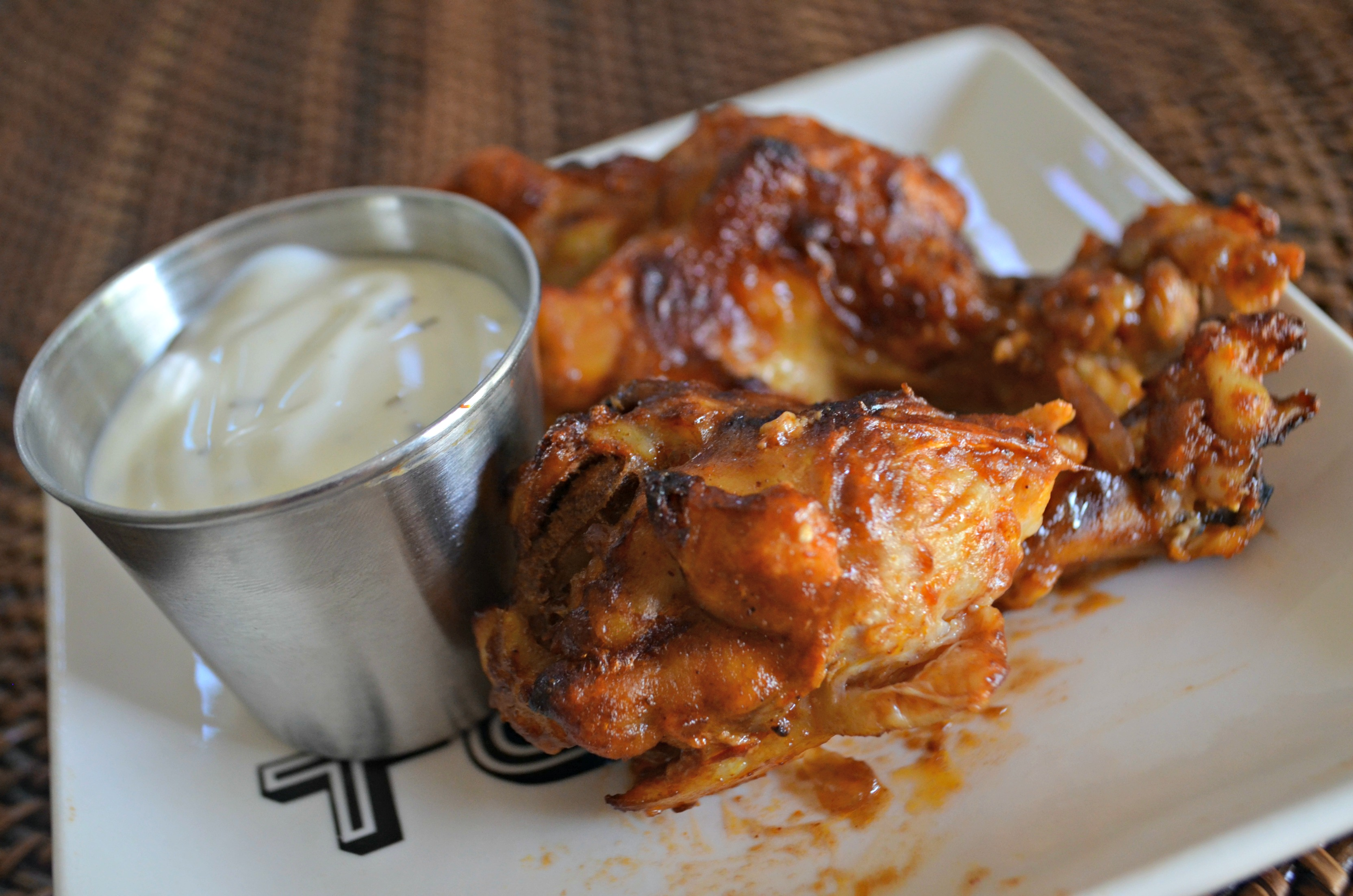 easy slow cooker buffalo bbq chicken wings - Wings on a plate with dipping sauce
