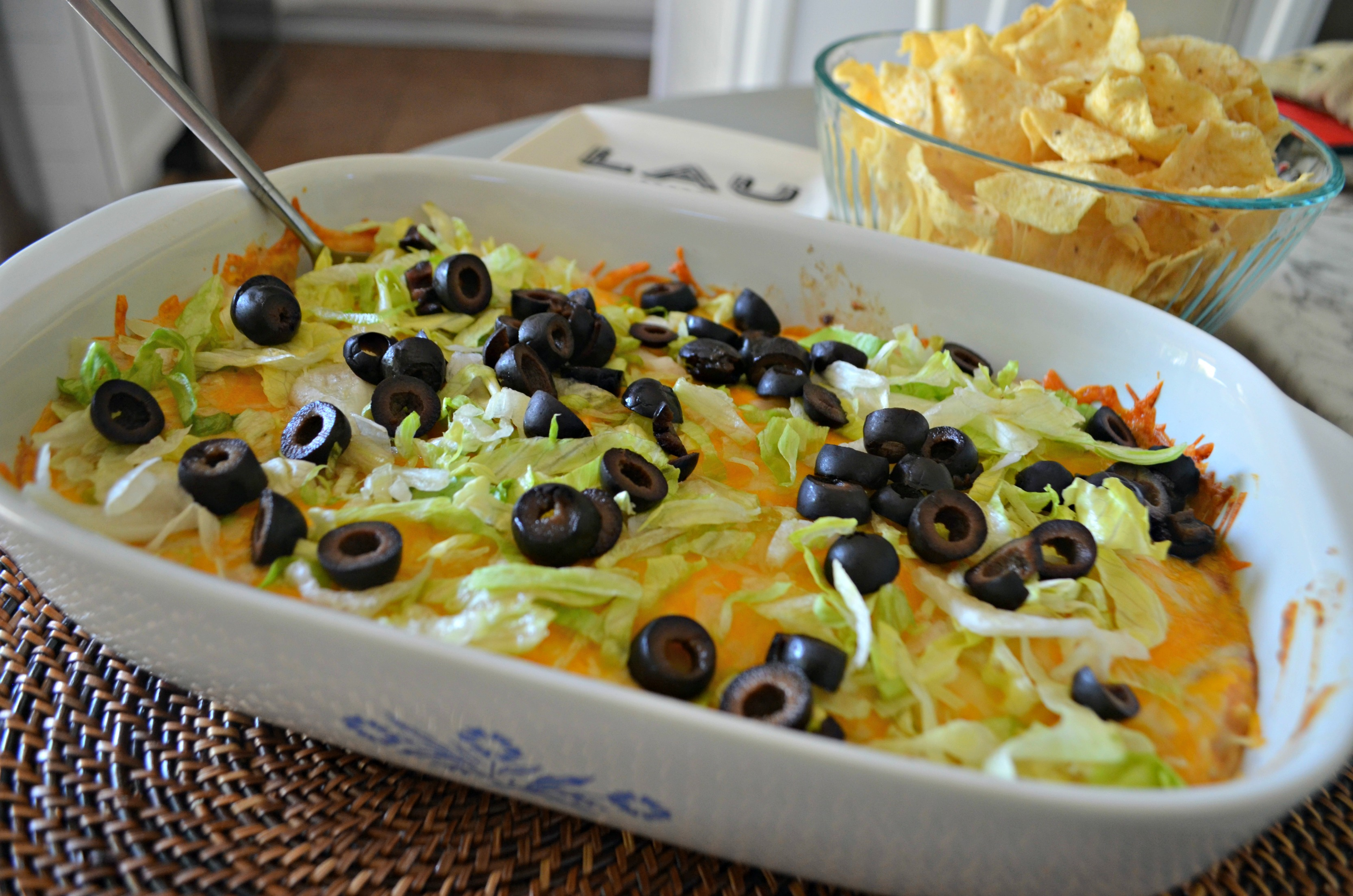 Baked taco dip with shredded lettuce and black olives on top.