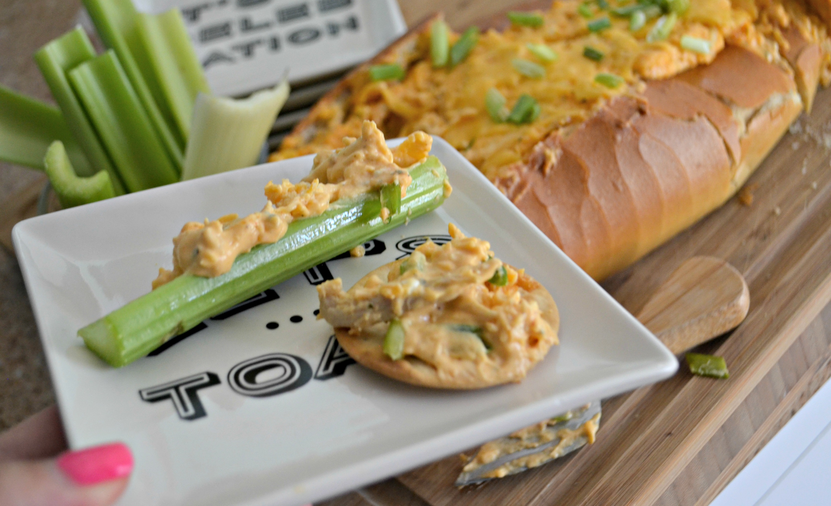 Buffalo Chicken Dip Bread Bowl - served on celery and a cracker