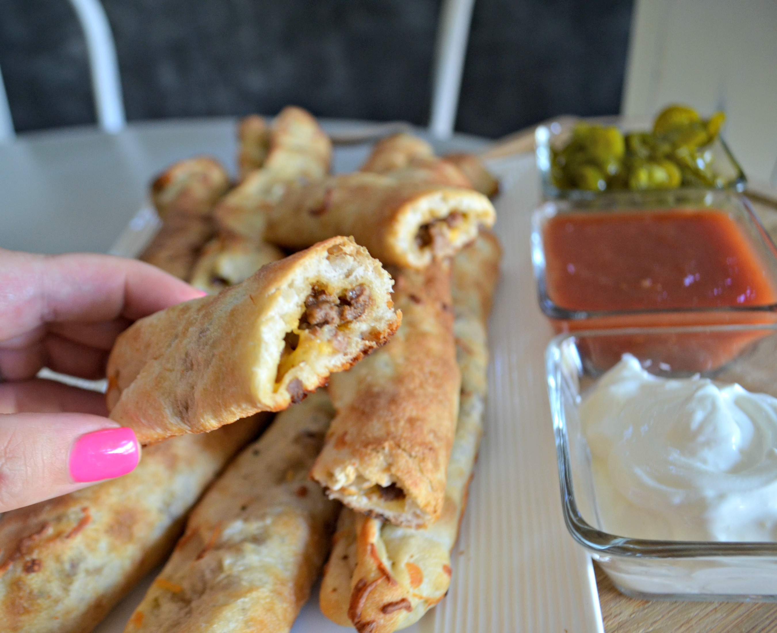 Easy 3 Ingredient Cheesy Taco Stuffed Breadsticks -after baking with the center showing from the end plus dipping sauces