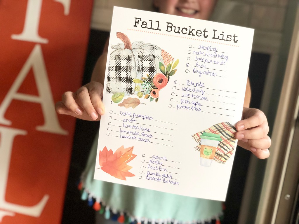 Our free printable fall bucket list filled out and held by a young girl