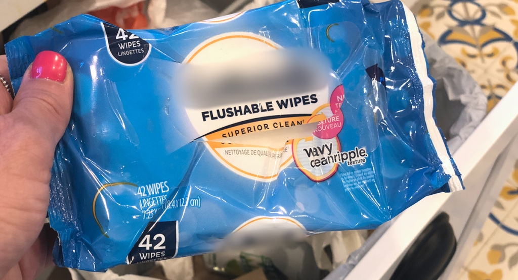 holding up flushable wipes package before being thrown out
