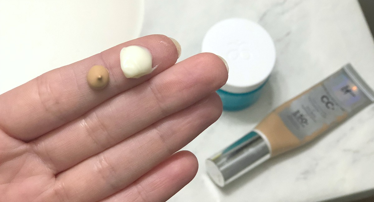 beige foundation and white cream on tip of finger
