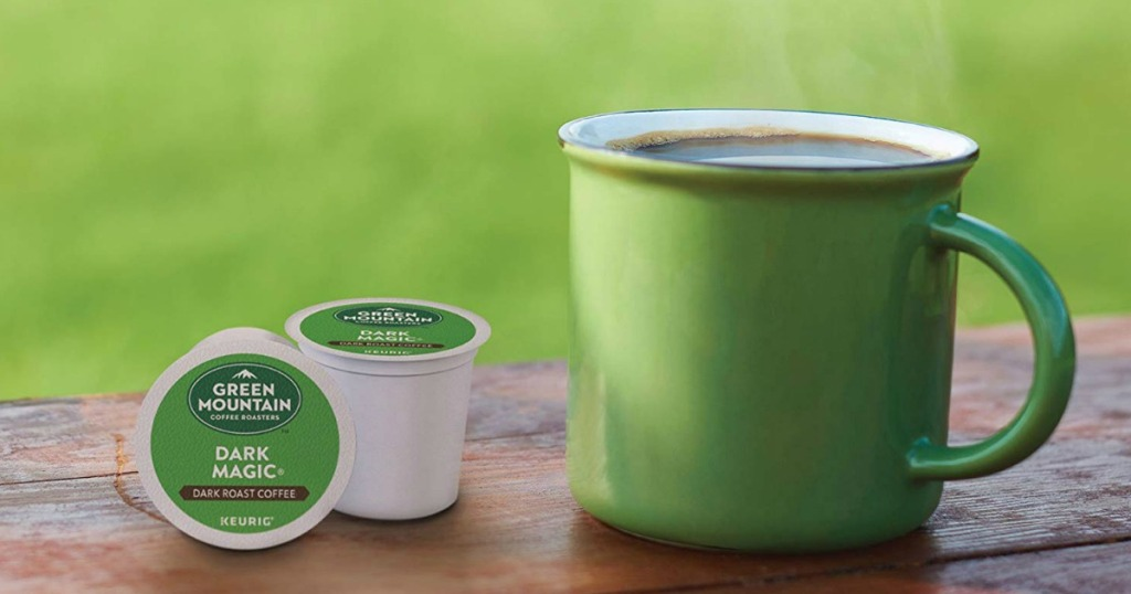 Green Mountain k-cups sitting on a table next to a mug of coffee