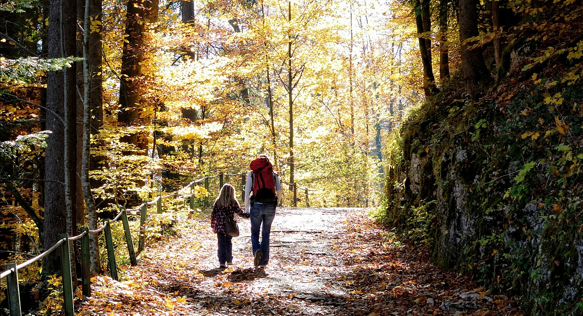 places for free fun fall activities — mother and daughter hiking trail with autumn leaves