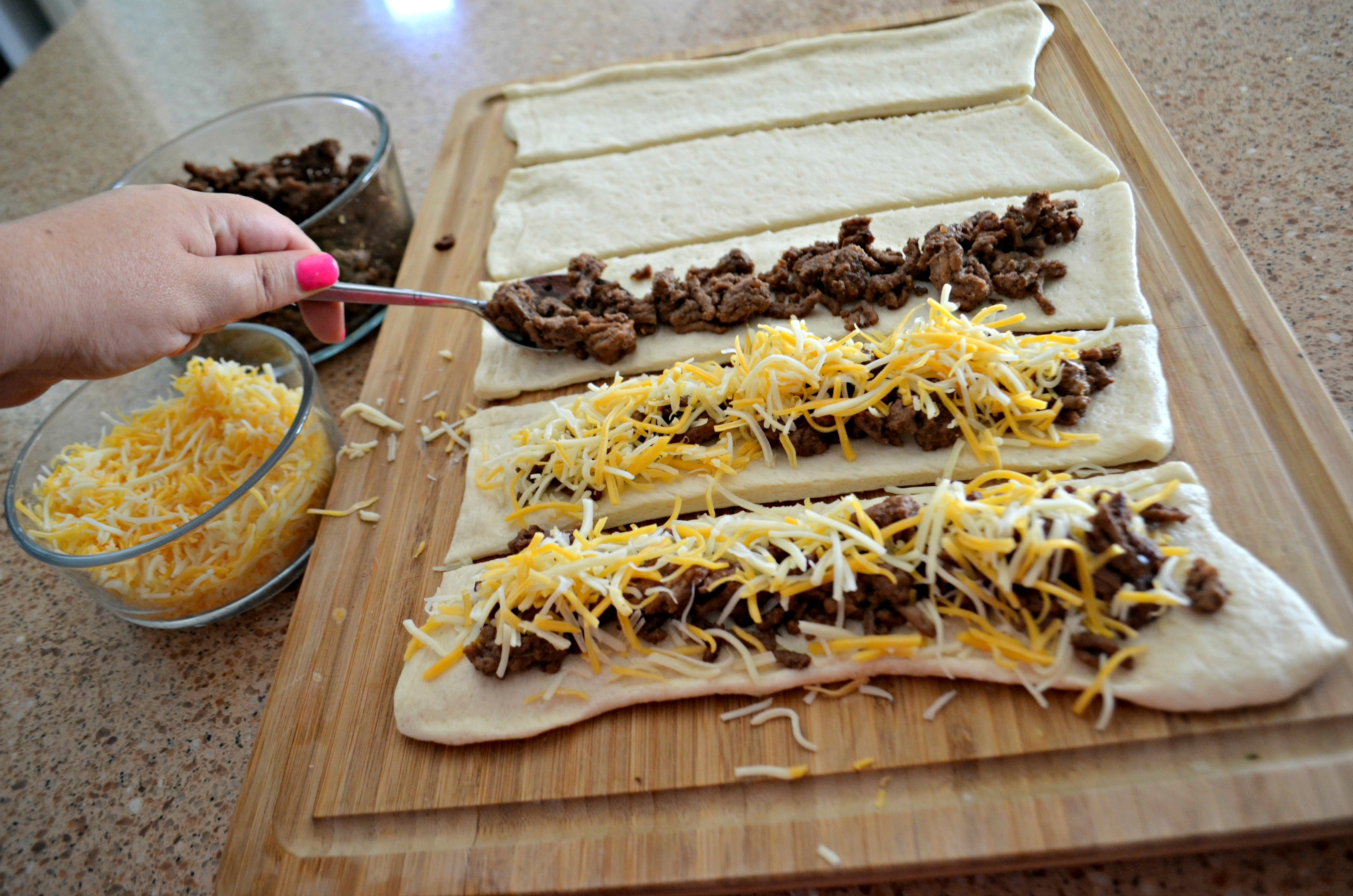 Easy 3 Ingredient Cheesy Taco Stuffed Breadsticks - assembling on a cutting board