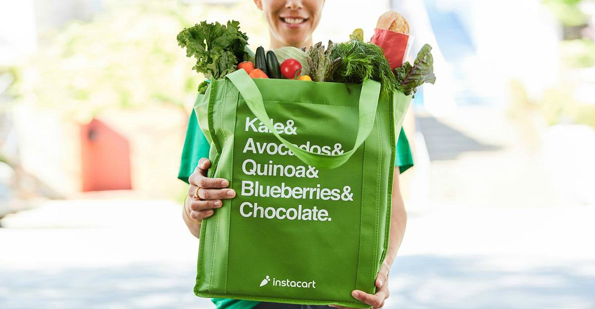 Online grocery pickup and delivery services —instacart shopper holding bag of groceries