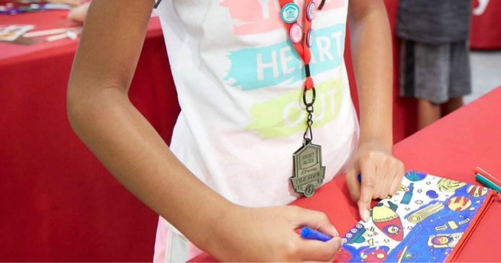 girl wearing a JCPenney lanyard coloring a pencil pouch