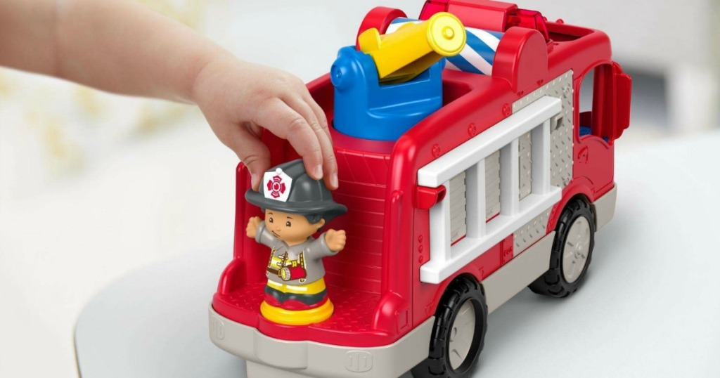 hand holding toy fireman on toy fire truck