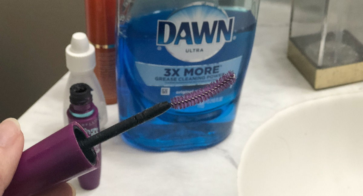 hand holding a purple mascara wand in front of blue dawn dish soap