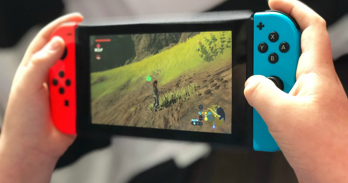 person holding nintendo switch console with red and blue joycons