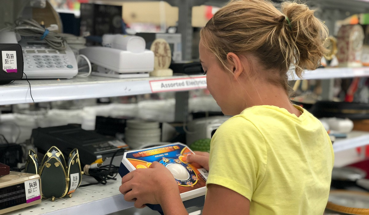 collin's deals and finds this week — piper looking at products on shelf at the thrift store