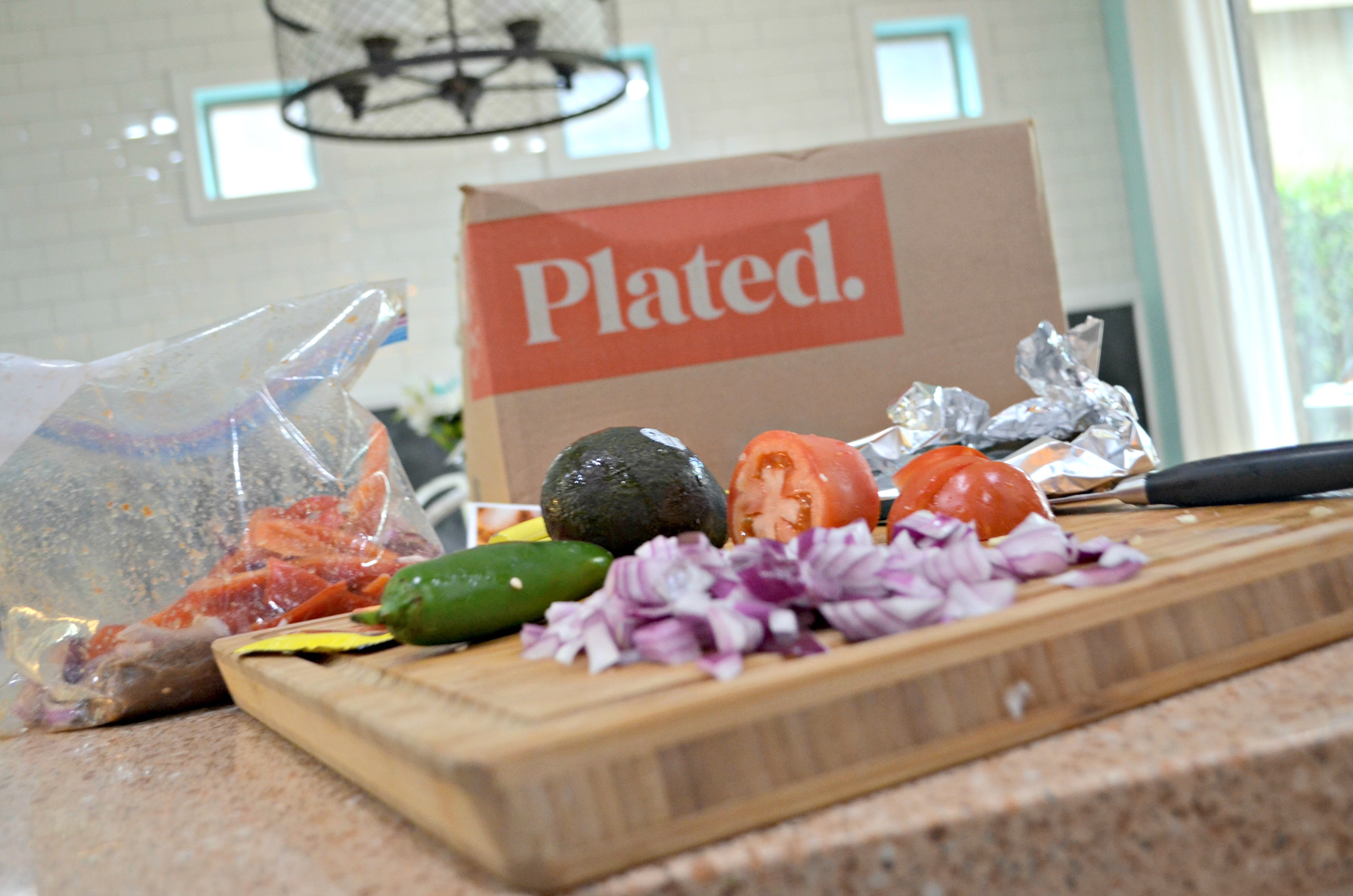 deal plated meal kit – Plated subscription box ingredients on a kitchen counter.