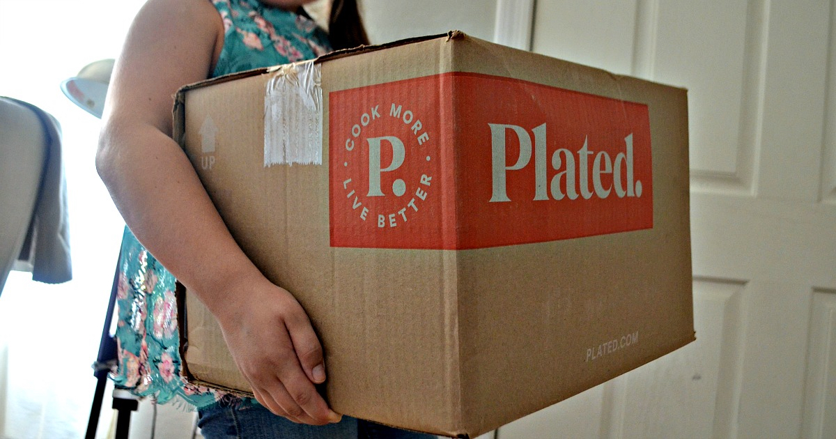 deal plated meal kit – Plated subscription box being carried in by a young woman.