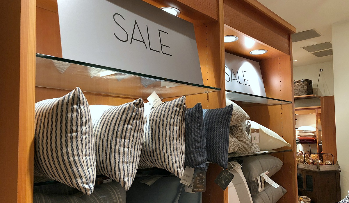 shop pottery barn with these money-saving tips – pottery barn wall of sale items with pillows on shelves