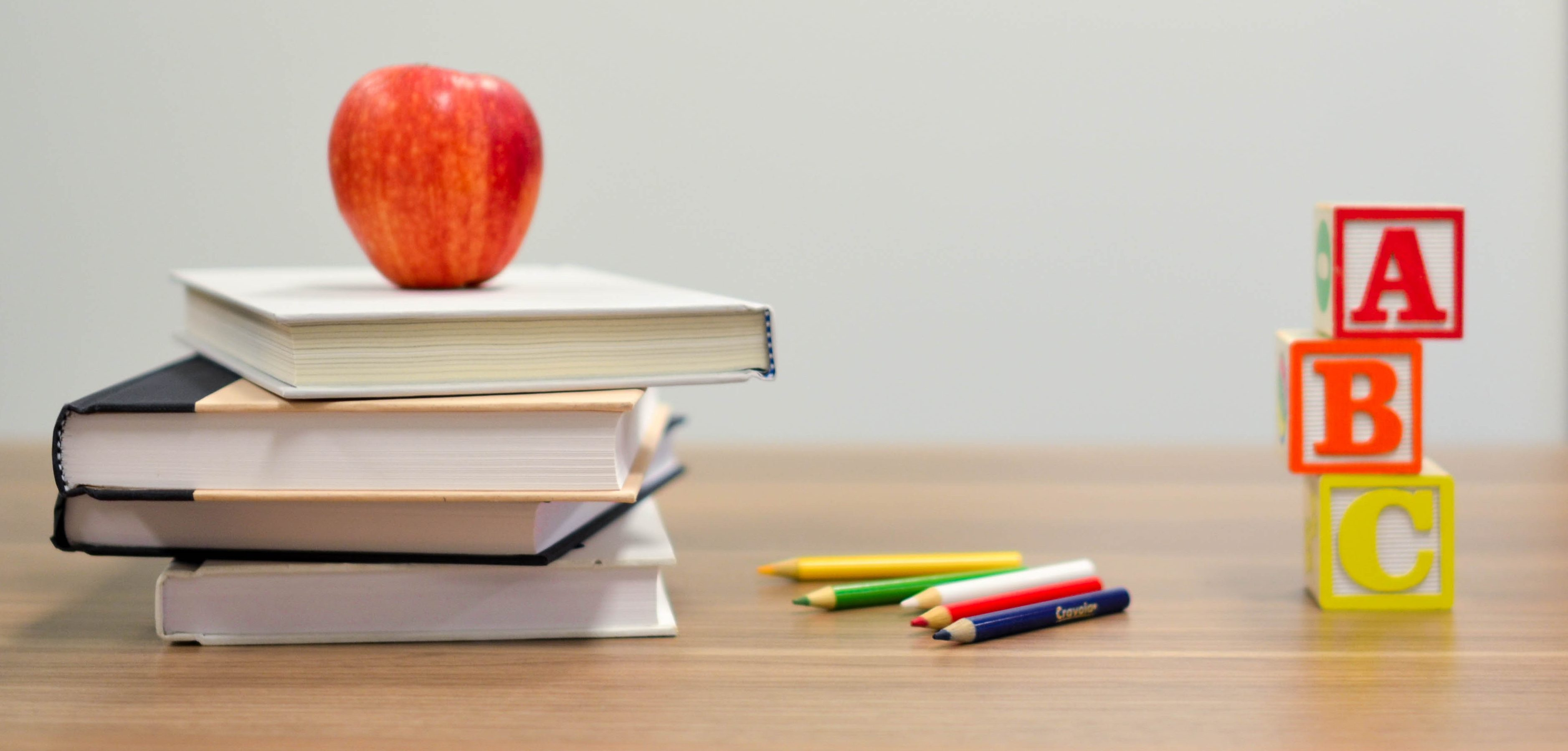 A suggested stack of books and an apple one might have when they earn money teaching English at home with SayABC.com.