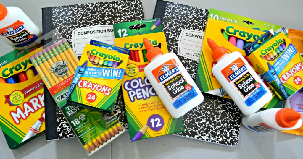 School supplies in a pile, including glue, pencils, composition notebooks, and crayons