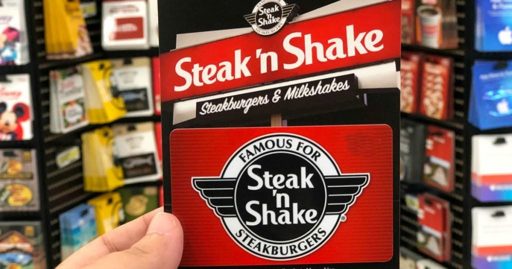hand holding a steak n shake gift card