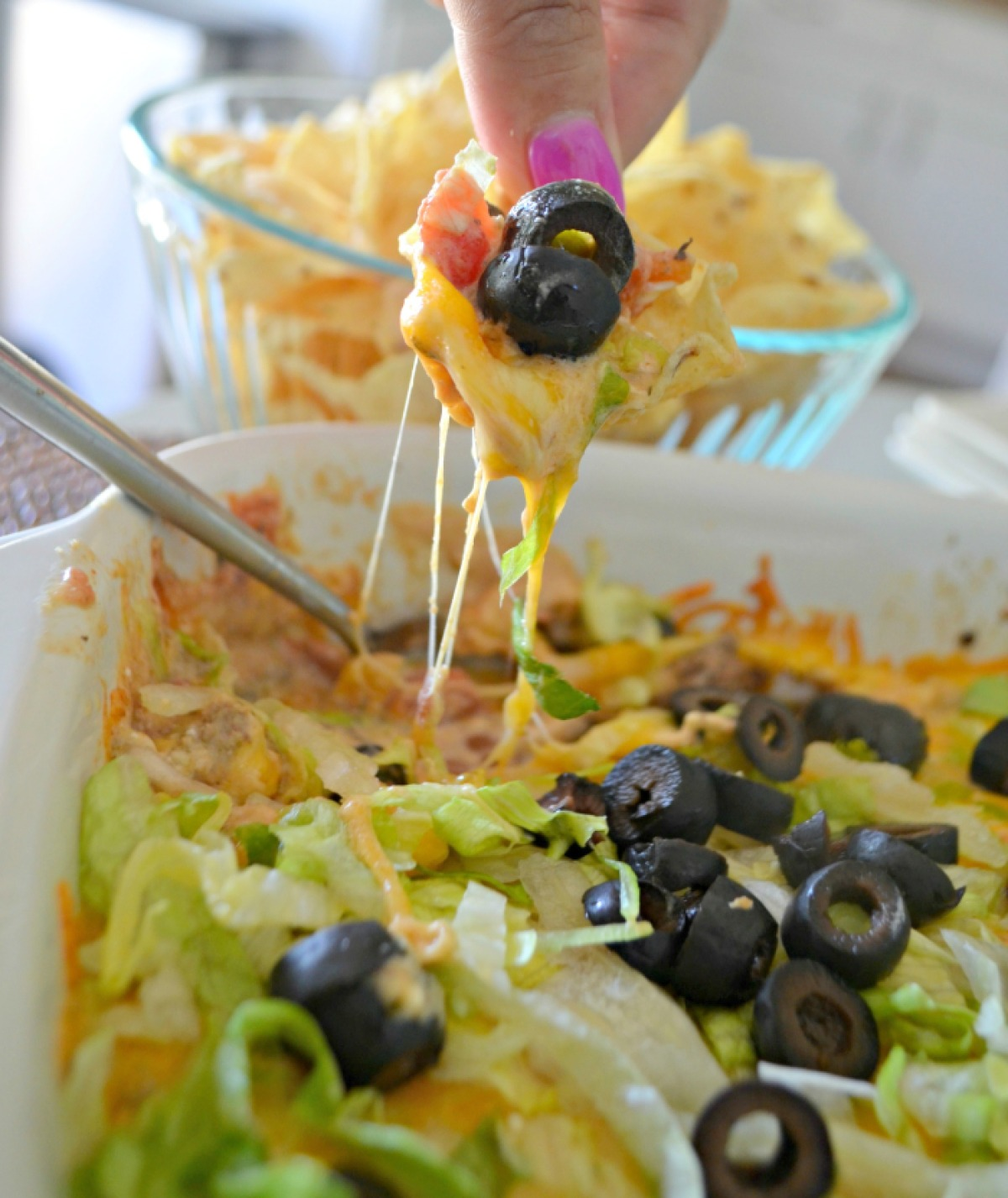 Scooping up baked taco dip with a chip.